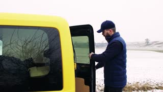 Delivery man delivering parcel box to recipient - courier service concept. A man with a smartphone making a phone call.