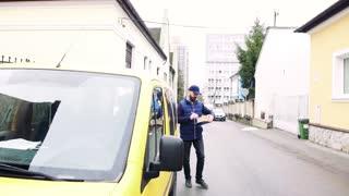 Delivery man delivering parcel box to recipient - courier service concept. Slow motion.