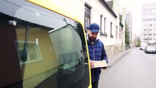 Delivery man delivering parcel box to recipient - courier service concept.