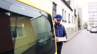 Delivery man delivering parcel box to recipient - courier service concept.