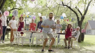Family celebration outside in the backyard. Big garden party. Slow motion.