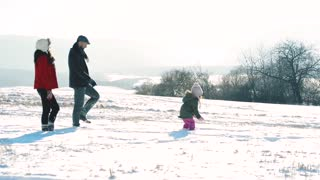 Father and mother with their daughter, walking in the snow.