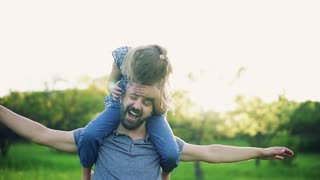 Father giving small daughter a piggyback ride in spring nature at sunset, having fun. Slow motion.