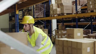 Female warehouse worker loading boxes.