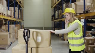 Female warehouse worker with smartphone.