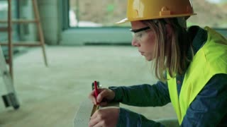 Female worker on the building site. Beautiful young woman measuring the building blocks. House construction. Slow motion