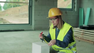 Female worker on the building site. Beautiful young woman measuring the building blocks. House construction