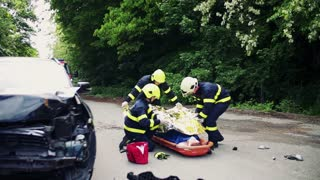 Firefighters helping a young woman after a car accident, putting a thermal blanket on her. A female driver in a plastic stretcher on the countryside road. Slow motion.