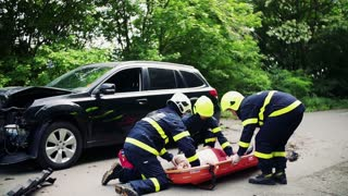 Firefighters putting a young injured woman into a plastic stretcher on the road after a car accident. Slow motion.