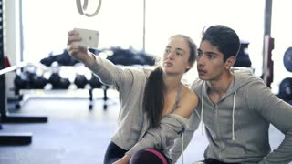 Fit couple in crossfit gym taking selfie with smartphone.
