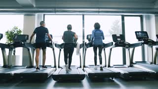 Fit seniors in gym on treadmills doing cardio work out.