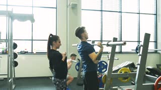 Fit young men in gym working out, lifting barbells