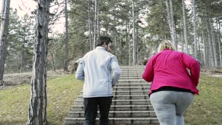 Fitness trainer in park running up the stairs with overweight woman.