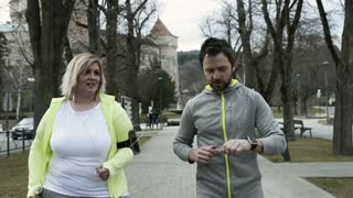 Fitness trainer in town park running with overweight woman.