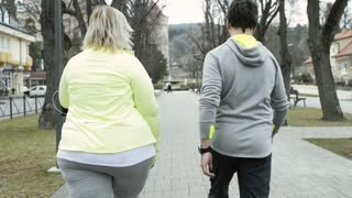 Fitness trainer running with attractive overweight blonde woman.