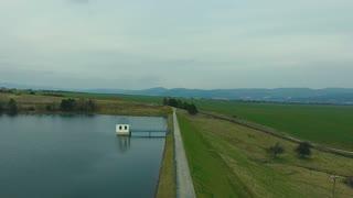 Green nature, flat plains and a lake.