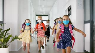 Group of cheerful children with face masks running and jumping on corridor, back to school concept.