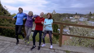 Group of senior runners posing outdoors in the old town.