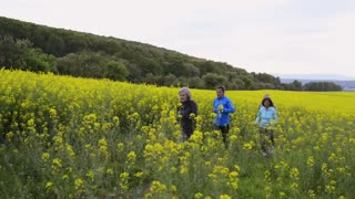 Group of seniors running outside in canola field.