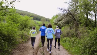 Group of seniors running race in nature on dirt road.