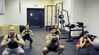 Group of young people in crossfit gym exercising together with kettlebells while doing squats