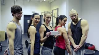 Group of young people in crossfit gym flexing arm muscles, taking selfie with smart phone