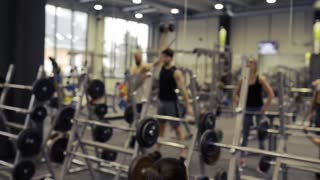 Group of young people in gym in front of mirror exercising together with various barbells