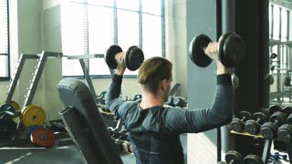 Handsome man in gym working out with weights