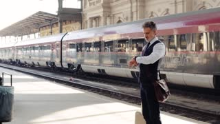 Handsome mature businessman in a city. Man waiting for the train at the railway station, checking the time. Slow motion
