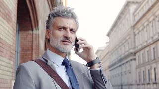 Handsome mature businessman with a smartphone in a city. Man making a phone call