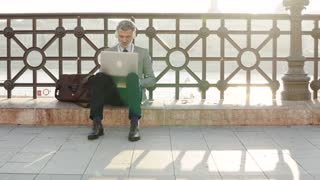 Handsome mature businessman with laptop in a city. Man sitting on a bridge, using headphones