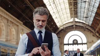 Handsome mature businessman with smartphone in a city. Man waiting for the train at the railway station, text messaging. Slow motion