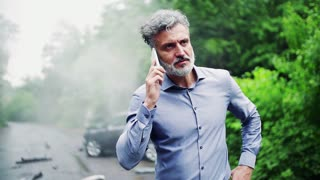 Handsome mature man making a phone call after a car accident, smoke in the background. Slow motion.