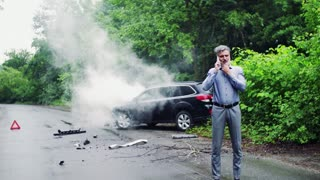 Handsome mature man making a phone call after a car accident, smoke in the background.