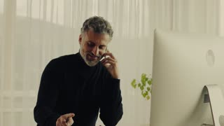 Handsome mature man with desktop computer and smartphone working in home office