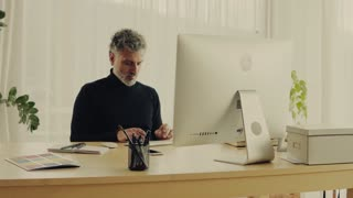 Handsome mature man with desktop computer working in home office