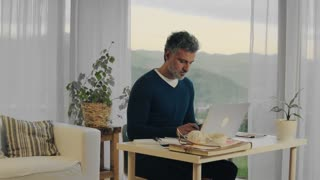 Handsome mature man with laptop working in home office