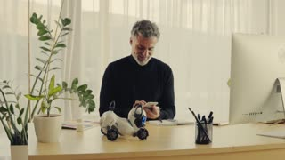 Handsome mature man with robot smart dog and smartphone in home office. Slow motion