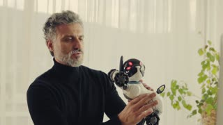Handsome mature man with robot smart dog in home office. Slow motion