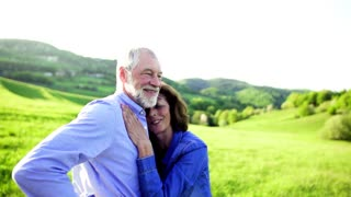 Happy relaxed senior couple outside in spring nature, hugging. Slow motion. Copy space.