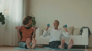 Happy senior couple relaxing at home, doing exercises. Slow motion
