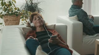 Happy senior couple with tablet and smartphone relaxing at home. A woman listening to music and a man holding a cup of coffee. Slow motion