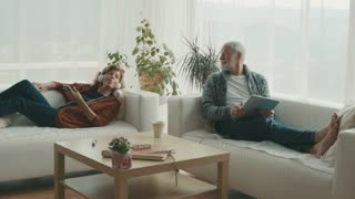 Happy senior couple with tablet and smartphone relaxing at home. Slow motion
