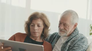Happy senior couple with tablet relaxing at home