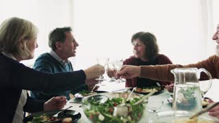Happy senior couples clinking glasses of wine at dinner time. Leisure time and celebration concept.