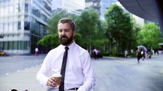 Hipster businessman sitting in the city, drinking coffee and checking the time. Slow motion.