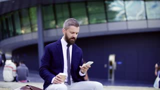 Hipster businessman with smartphone sitting on a bench on the street in London, text messaging and drinking coffee. Slow motion.