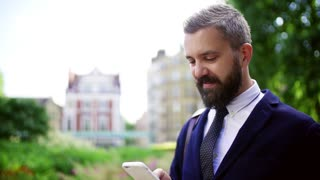 Hipster businessman with smartphone standing on the street in city, text messaging. Slow motion.