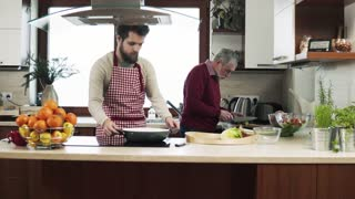 Hipster son with his senior father cooking in the kitchen. Two generations indoors.