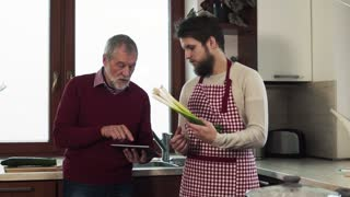 Hipster son with his senior father with tablet in the kitchen.